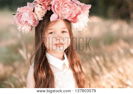 Smiling baby girl 3-4 year old posing with flowers in hairstyle outdoors. Summer portrait. Childhood.