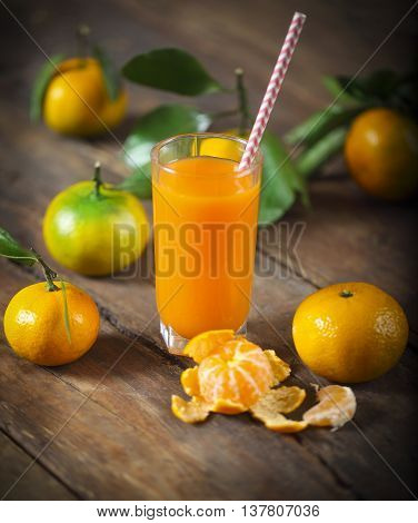 Glass of fresh tangerine juice with ripe tangerines leaves and old-fashioned straw