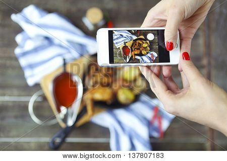 Woman taking a photo of a hot meat dishes on the wooden background with smaatphone. Grilled chicken wings with red spicy sauce