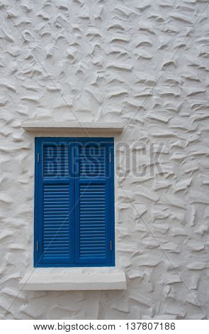 The blue wooden window frame on building stucco wall at home