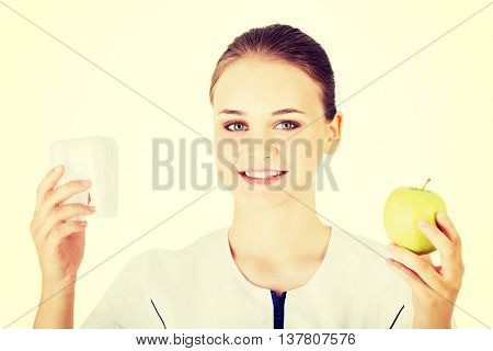 Doctor smiling , holding tooth and apple.