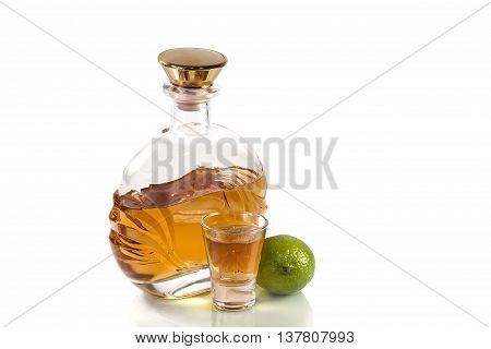 Bottle of tequila and a shot glass with a lime on a white background