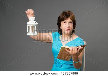 Mature student woman with book and lantern on dark background