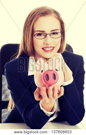 Beautiful business woman with piggy bank.