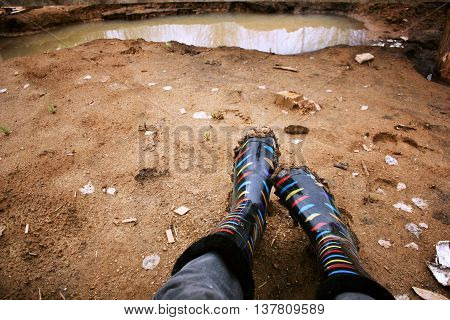 Legs in colored rubber boots soiled with clay amid puddles.
