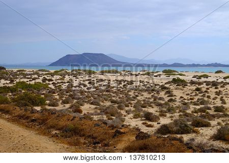 View on the beach Corralejo with sand dunes in the natural park and on the island Lobos. Location Fuerteventura, Spain.