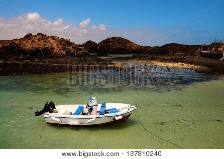 A boat in a lagoon with emerald water on the island Lobos, Spain.