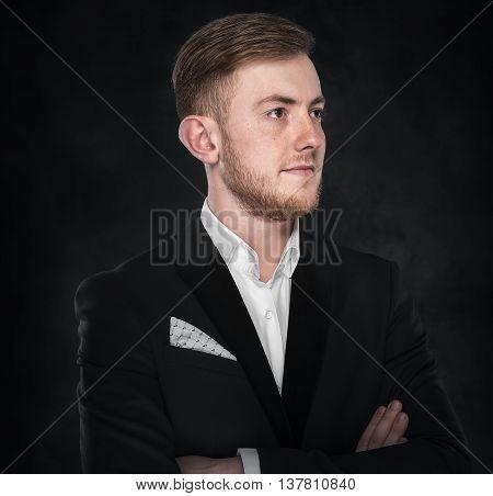 Businessman in suit standing on dark background.