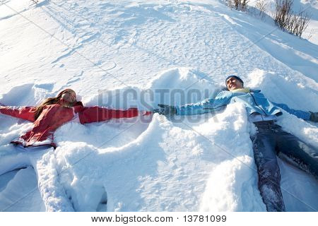 Photo of happy guy and joyful girl lying in snowdrift during winter vacation