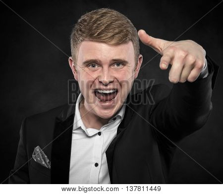 Young business man pointing at the camera and shouts, on dark background.