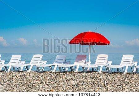 Sun Umbrella And Beach Beds On The Shingle Beach