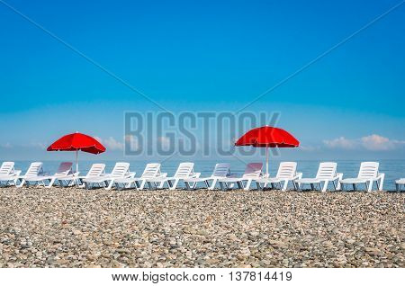 Sun Loungers And Red Umbrellas On The Beach In Batumi