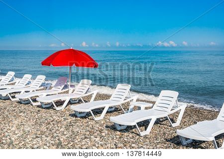 Sunbathing Plastic Beds And Red Umbrella On The Beach