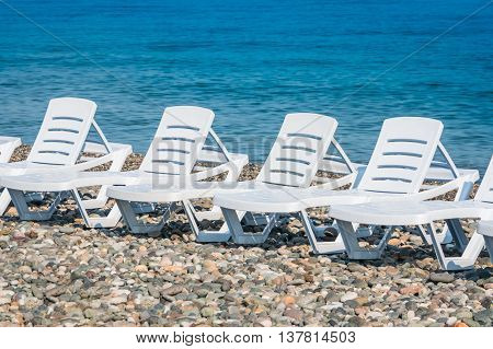 Four White Plastic Beach Chairs On The Beach