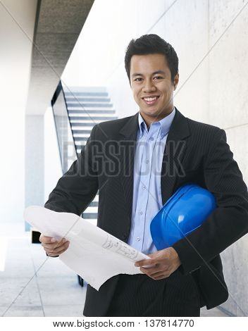 Happy Asian architect holding floor plan and hardhat, smiling, looking at camera.