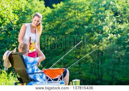 Couple of woman and man having a beer while sport fishing on the lakeside