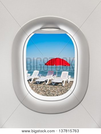 Looking Out The Window Of A Plane To The Sunbeds And Umbrella