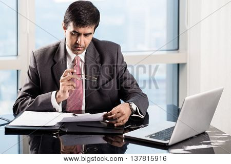 Indian Senior Executive in his skyscraper office, reading business contracts