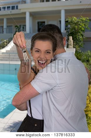Happy young couple with keys in front of their completed new home