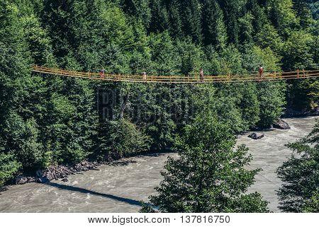 Upper Svanetia Georgia - July 25 2015. Tourists walks on the suspension bridge over Inguri River in Svenetia region of Georgia