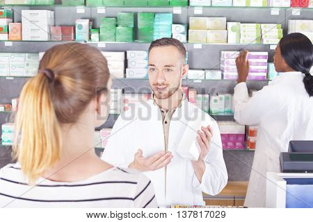 Male Pharmacist attending female customer in pharmacy