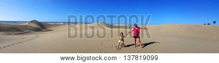 mother and daughter in Sandy dunes in famous natural Maspalomas beach. Gran Canaria. Spain