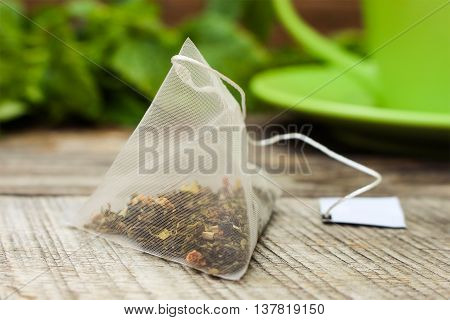 Tea bag on background of mint and and green cup