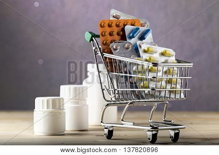 Shopping cart filled with blister packs of colorful pills