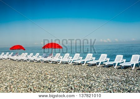 Sun Loungers And Red Umbrellas On The Beach