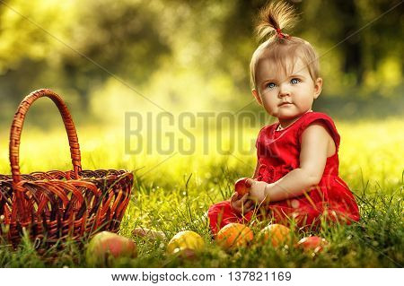 Little girl in red dress sitting on the grass with basket and fruits