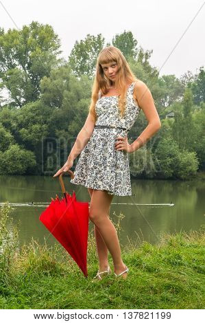 Young Lady With Red Umbrella Near The Pond