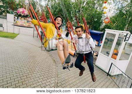 Emotional newlyweds screaming while riding on high carousel in amusement park. Expressive wedding couple at carnival