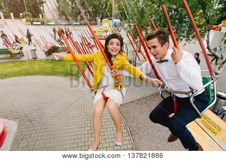 Frightened bride on high carousel with eyes wide opened. Emotional wedding couple in amusement park, carnival. Fear of heights concept