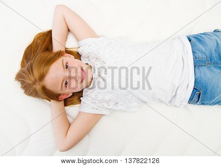 Young girl is lying on the bed. Quality mattress.
