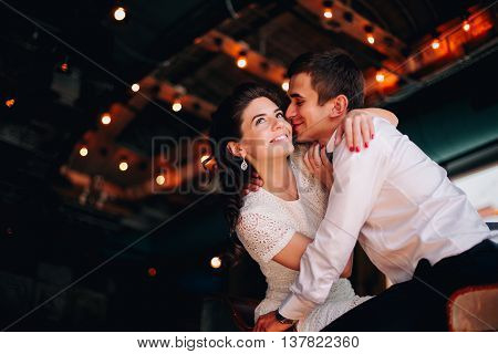 The groom kisses his bride in vintage interior. She smiles and dreamily ooks up