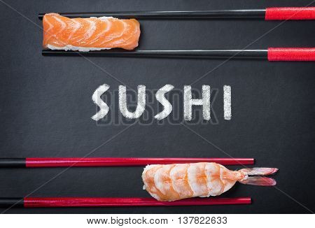 close-up of chopsticks and two sushi and an inscription on a black background