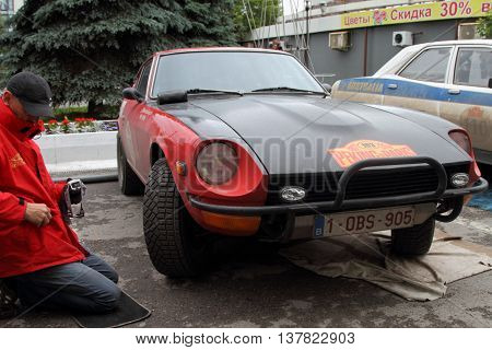 PERM RUSSIA - JUNE 29 2016: Rally of retro-cars Peking-Paris 2016 June 29 2016 in Perm Russia. Participant rally Datsun 240Z repairs.