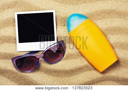 photo frame sunblock and sunglasses on sand