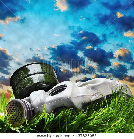 old gas mask lying on the grass against the smoky sky