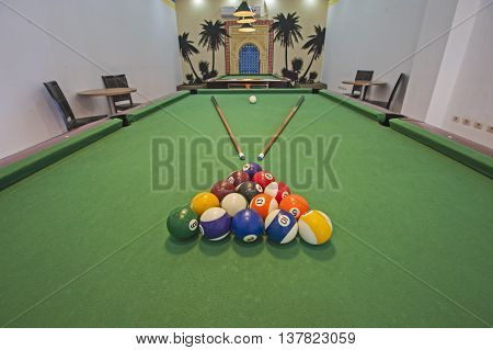 Closeup of billiard balls on green felt table with pool cues in games room