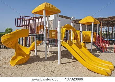 Chlildrens climbing frame with slide on sand in tropical hotel resort kids playground