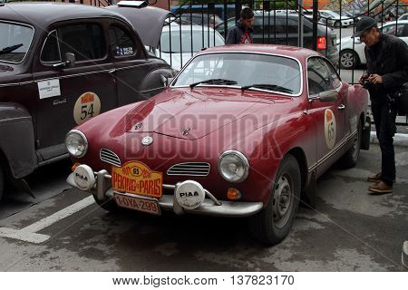 PERM RUSSIA - JUNE 29 2016: Rally of retro-cars Peking-Paris 2016 June 29 2016 in Perm Russia. Residents of the city visiting the car Volkswagen Karmann Ghia of race participants