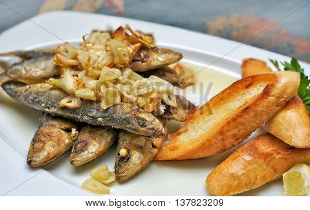 Fried sardines with garlic, grilled toast bread