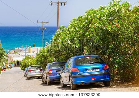 BALI, GREECE - APRIL 29, 2016: Rental car Peugeot 206 are parked on the sloping street leading to the sea about office leasing transport. Resort village Bali, Rethymno, Crete, Greece