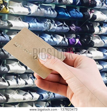 woman's hand holding a credit card in the background supermarket shelves