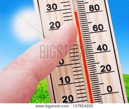 Thermometer in hand shows a strong heat of the summer landscape background