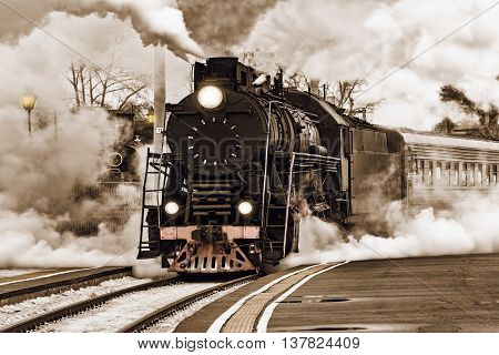 Retro steam train departs from the station.