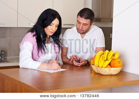 Couple Writing And Calculate Their Expenses