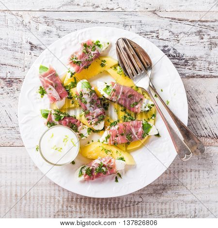 Rolls of mozzarella, basil and Parma ham on slices of mango with yoghurt sauce on white plate. Healthy eating concept with copy space