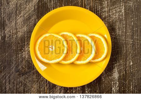 Orange slices in a yellow plate top view